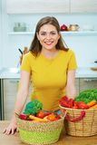 Portrait of young woman in kitchen with wegetables. Healthy foo Stock Images