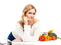 Portrait of a young woman in a kitchen on white Stock Photo