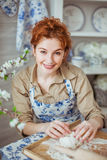 Portrait of a young woman kneads a dough on Royalty Free Stock Photo