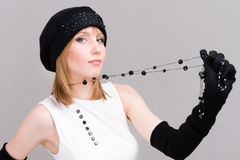 Woman in knit wool hat with black necklace. Portrait of a young woman in knit wool hat and mittens with black necklace.  on gray background Royalty Free Stock Photography