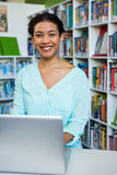 Portrait of young woman with laptop in library Stock Image