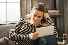 Portrait of young woman is laying on couch and holding tablet Royalty Free Stock Photo