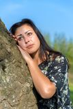 Portrait woman leaning against tree trunk. Portrait young woman leaning against tree trunk Royalty Free Stock Photography
