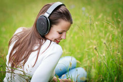 Portrait of  young woman listening to Royalty Free Stock Image