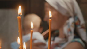 Portrait of young woman with little boy behind the candles in church stock footage
