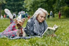 A Portrait of a young woman with a little dog. Portrait of a young woman with a little dog. She is reading a book royalty free stock image