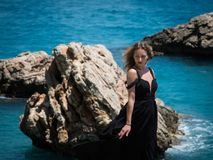Young woman in black dress on the rocks Royalty Free Stock Image