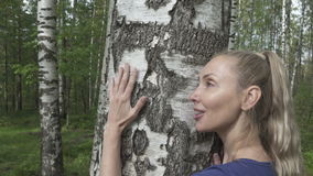 Portrait of the young woman with a long fair hair of the birch embracing a trunk in the birch wood.  stock video footage