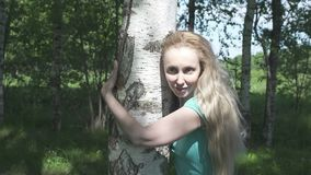 Portrait of the young woman with a long fair hair of the birch embracing a trunk in the birch wood.  stock video