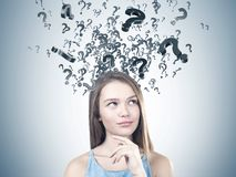 Young pensive woman, many questions. Portrait of a young woman with long fair hair wearing a blue dress and thinking. Many black question marks emerging from her Royalty Free Stock Images