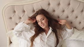 Portrait of a young woman with long red hair in bed in the morning. Portrait of a young woman with long red hair in bed in the morning, she is wearing a white stock video footage