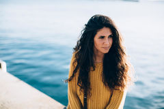 Portrait of young woman looking away while sitting on pier Royalty Free Stock Photo