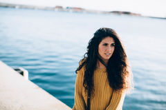 Portrait of young woman looking away while sitting on pier Royalty Free Stock Image