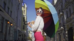 Portrait young woman looking at the camera holding multicolored umbrella standing on the street. Attractive fashionable. Positive beautiful young woman looking stock video footage