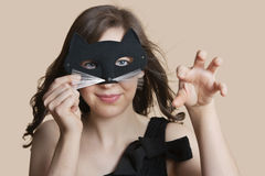 Portrait of a young woman looking through eye mask imitating as cat over colored background Royalty Free Stock Photography