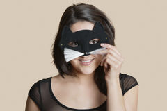 Portrait of a young woman looking through eye mask over colored background Stock Photo