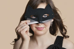 Portrait of a young woman looking through eye mask over colored background Royalty Free Stock Photo
