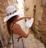 Portrait of young woman looking at map on old narrow street Stock Image