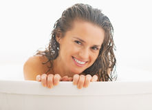 Portrait of young woman looking out from bathtub Royalty Free Stock Photo