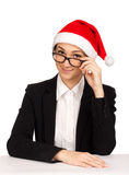 Portrait of young woman looking over glasses. Portrait of young woman in santa hat looking over glasses Royalty Free Stock Photos