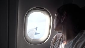 Portrait of young woman is looking at plane window. stock video