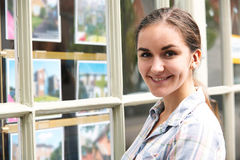Portrait Of Young Woman Looking In Window Of Estate Agent Stock Photography