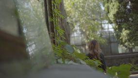 Portrait of young woman looking in the window of the old house while walking in the garden. Concept of summertime. Femininity, curiosity stock footage
