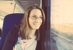 Portrait of young woman looking through window. Traveling by train Royalty Free Stock Photo