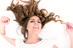 Portrait of young woman lying in bed with hair spread around. Portrait of young casual woman lying in bed with hair spread around, domestic atmosphere royalty free stock photos