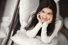 Portrait of a young woman lying in bed at the window. Stock Images