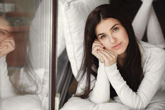 Portrait of a young woman lying in bed at the window. Stock Photo