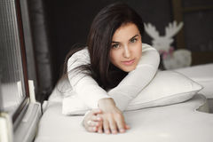 Portrait of a young woman lying in bed at the window. Royalty Free Stock Photo