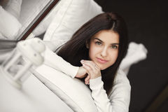 Portrait of a young woman lying in bed at the window. Royalty Free Stock Photos