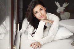 Portrait of a young woman lying in bed at the window. Royalty Free Stock Image
