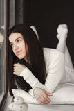 Portrait of a young woman lying in bed at the window. Stock Photos