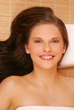 A portrait of a young woman lying down. A portrait of a smiling young woman lying down Stock Photography
