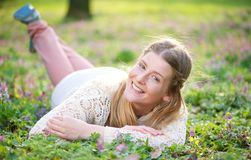 Portrait of a young woman lying on grass outdoors Royalty Free Stock Photography