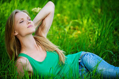 Portrait young woman lying green grass Stock Photography
