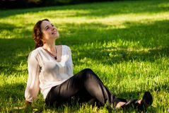 Portrait of young woman lying on a green lawn Royalty Free Stock Photography
