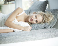 Portrait of young woman lying on sofa at home Royalty Free Stock Images