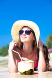 Portrait of young woman lying in straw hat in Stock Images