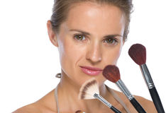 Portrait of young woman with makeup brushes Stock Images