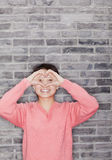 Portrait of Young Woman Making Heart with Fingers, Looking At Camera Stock Photo