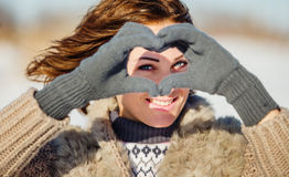 Portrait of young woman making heart symbol Stock Photography