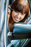 Portrait of young woman making herself up in car Royalty Free Stock Photo