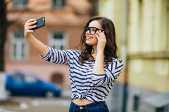 Portrait young woman making selfie on mobile phone Stock Images