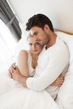 Portrait of young woman with man embracing in hotel room Stock Photos