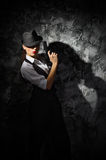 Portrait of young woman in manly style with gun at grey wall Royalty Free Stock Photo