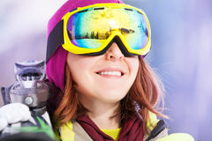 Portrait of young woman in mask holding ski. Portrait of young woman in mask standing and holding ski during winter day on Krasnaya polyana ski resort and Royalty Free Stock Image