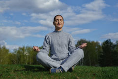 Portrait of young woman meditating in pose of lotus on green grass outdoor Royalty Free Stock Photo